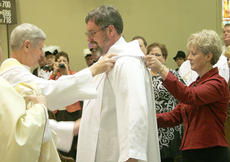 "<div class=""source"">Photos submitted by Debbie Glasscock</div><div class=""image-desc"">Fr. Jerry Bell and Cheryl May help Dennis May with his stole during his ordination as a deacon Feb. 19. </div><div class=""buy-pic""></div>"