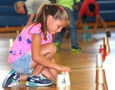 """<div class=""""source"""">Stevie Lowery</div><div class=""""image-desc"""">Aubri Wayne concentrates as she participates in a cup stacking activity. </div><div class=""""buy-pic""""><a href=""""http://web2.lcni5.com/cgi-bin/c2newbuyphoto.cgi?pub=015&orig=07-23-14_ges_summer_camp_1_0.jpg"""" target=""""_new"""">Buy this photo</a></div>"""