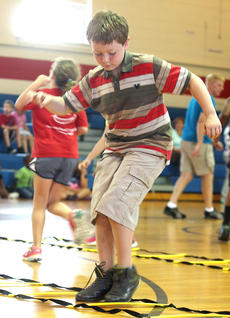 """<div class=""""source"""">Stevie Lowery</div><div class=""""image-desc"""">Timothy Sherrell weaves in and out of the agility ladder during a physical education exercise. </div><div class=""""buy-pic""""><a href=""""http://web2.lcni5.com/cgi-bin/c2newbuyphoto.cgi?pub=015&orig=07-23-14_ges_summer_camp_6_0.jpg"""" target=""""_new"""">Buy this photo</a></div>"""