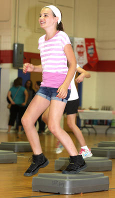 """<div class=""""source"""">Stevie Lowery</div><div class=""""image-desc"""">Michaela May smiles as she jumps on and off a """"fitness box."""" </div><div class=""""buy-pic""""><a href=""""http://web2.lcni5.com/cgi-bin/c2newbuyphoto.cgi?pub=015&orig=07-23-14_ges_summer_camp_9.jpg"""" target=""""_new"""">Buy this photo</a></div>"""