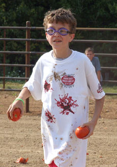 """<div class=""""source"""">Stephen Lega</div><div class=""""image-desc"""">Aiden Freihart approaches the opposing side, tomatoes at the ready. </div><div class=""""buy-pic""""><a href=""""http://web2.lcni5.com/cgi-bin/c2newbuyphoto.cgi?pub=015&orig=07-30-14_tomato_conflict_pic_8.jpg"""" target=""""_new"""">Buy this photo</a></div>"""