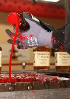 """<div class=""""source"""">Stephen Lega</div><div class=""""image-desc"""">Jenny Spannknebel spins to """"cut the tail"""" after dipping it in Maker's Mark's signature red wax. </div><div class=""""buy-pic""""><a href=""""http://web2.lcni5.com/cgi-bin/c2newbuyphoto.cgi?pub=015&orig=08-27-14_bottling_line_pic_4.jpg"""" target=""""_new"""">Buy this photo</a></div>"""