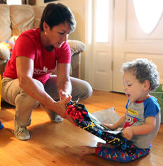 """<div class=""""source"""">Stevie Lowery</div><div class=""""image-desc"""">Eli opens a birthday present from Cindy Robinson, a physical therapist with First Steps, who has been working with him once a week, every week, since he was six months old. </div><div class=""""buy-pic""""><a href=""""/photo_select/57844"""">Buy this photo</a></div>"""