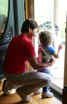 """<div class=""""source"""">Stevie Lowery</div><div class=""""image-desc"""">Eli watches it rain out the front door and calls for his doggies while Cindy Robinson, a physical therapist with First Steps, helps him keep his balance. </div><div class=""""buy-pic""""><a href=""""/photo_select/57845"""">Buy this photo</a></div>"""