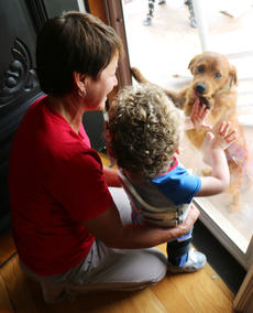 """<div class=""""source"""">Stevie Lowery</div><div class=""""image-desc"""">Eli watches it rain out the front door and calls for his doggies while Cindy Robinson, a physical therapist with First Steps, helps him keep his balance. </div><div class=""""buy-pic""""><a href=""""/photo_select/57846"""">Buy this photo</a></div>"""