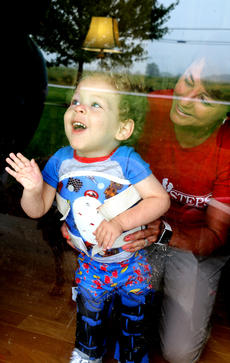"""<div class=""""source"""">Stevie Lowery</div><div class=""""image-desc"""">Eli watches smiles at his mother, Natalie Wheatley, at the front door while Cindy Robinson, a physical therapist with First Steps, helps him keep his balance.</div><div class=""""buy-pic""""><a href=""""/photo_select/57847"""">Buy this photo</a></div>"""