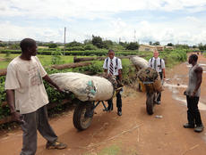 """<div class=""""source"""">Photo submitted</div><div class=""""image-desc"""">During his mission trip, Cook and his mission partners tried to find ways to help whenever they could, such as helping these two men push their wheelbarrows down the road. </div><div class=""""buy-pic""""></div>"""