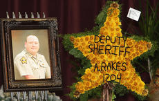"<div class=""source"">Stevie Lowery</div><div class=""image-desc"">A photo of Deputy Anthony Rakes and a flower arrangement in the shape of a sheriff's badge adorned his casket during his funeral service Saturday afternoon at Marion County High School.</div><div class=""buy-pic""><a href=""http://web2.lcni5.com/cgi-bin/c2newbuyphoto.cgi?pub=015&orig=11-21-12%2Brakes%2Bfuneral%2Bflower%2Bbadge.jpg"" target=""_new"">Buy this photo</a></div>"