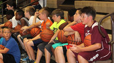 """<div class=""""source"""">Nick Schrager</div><div class=""""image-desc"""">A group of boys rest while watching their peers play on.</div><div class=""""buy-pic""""><a href=""""http://web2.lcni5.com/cgi-bin/c2newbuyphoto.cgi?pub=015&orig=6-26%2Bbball%2Bcamp%2B9.jpg"""" target=""""_new"""">Buy this photo</a></div>"""