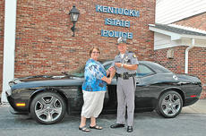 """<div class=""""source"""">Photo submitted</div><div class=""""image-desc"""">Latisa Roark, left, of Raceland, received the keys to a 2012 Dodge Challenger R/T Classic from Kentucky State Police Commissioner Rodney Brewer at KSP headquarters in Frankfort on Sept. 27. Roark won the vehicle in a raffle held by KSP on Aug. 26 at the Kentucky State Fair. Each year KSP sells raffle tickets to raise funds to support Trooper Island, a free summer camp for underprivileged boys and girls aged 10-12 operated by KSP on Dale Hollow Lake in Clinton County.  This year the raffle raised $127,978.40 for the camp. </div><div class=""""buy-pic""""></div>"""