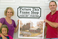 "<div class=""source"">Photo submitted</div><div class=""image-desc"">Picture This Frame Shop in Loretto held a drawing July 4 for a Maker's Mark fall print. The winner was Dee Dee Masterson. Pictured are, from left, Dee Dee Masterson, with her daughter Bethany, and Keith Bickett, owner.</div><div class=""buy-pic""></div>"