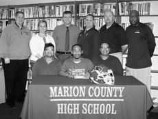 """<div class=""""source"""">submitted</div><div class=""""image-desc"""">Jordan Bell, pictured with his mother April Bell and aunt Anissa Cooper, signs a letter of intent to play football at Lindsey Wilson College.  Standing, from left, are Coach Chris Oliver, head football coach at Lindsey Wilson College, Christina McCray, assistant principal, Chris Brady, interim principal, Robby Peterson, Marion County assistant coach, Jeff Robbins, Marion County football head coach, and Anthony Epps, Marion County assistant coach.</div><div class=""""buy-pic""""></div>"""