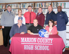 "<div class=""source"">submitted</div><div class=""image-desc"">Dylan Caldwell, pictured with parents George and Becky, signs a letter of intent to play football at Lindsey Wilson College.  Standing, from left, are Coach Chris Oliver, head football coach at Lindsey Wilson College, Christina McCray, assistant principal, Chris Brady, interim principal, Robby Peterson, Marion County assistant coach, Jeff Robbins, Marion County football head coach, and Anthony Epps, Marion County assistant coach. </div><div class=""buy-pic""></div>"