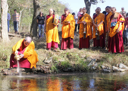 Buddhist monks from the Labrang Tashi Kyil Monastery visited Marion County in October. Lama Kunzang Tenphel pours the sand into the waters at Pope's Creek Ranch. The sand was used to create a mandala at the Marion County Public Library, which was destroyed in a special ceremony.