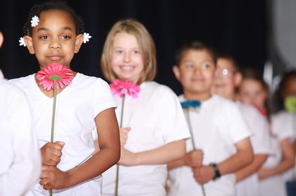 "Lexus Moffitt, Kaylee Leake and Noe Serrano held flowers at the start of the first graders' routine to ""Count on Me"" by Bruno Mars during the Glasscock Elementary School student showcase."