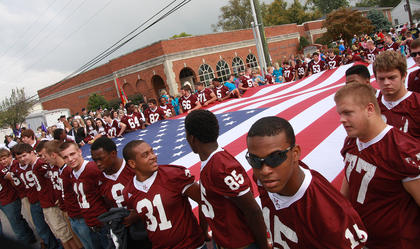 The Marion County High School football team lined up near the Marion County Public Library to carry a big American flag in the Spring View Hospital Pigasus Parade.