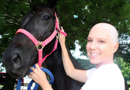 "Amy Thomas, 31, was diagnosed with breast cancer on Feb. 14 - Valentine's Day. She's had a double mastectomy and underwent chemotherapy treatments. Thomas is pictured with her horse, Misty, who is wearing a bright pink halter in honor of breast cancer awareness. She said riding and being around her horses is very therapeutic. ""My horses are a big part of who I am,"" she said."