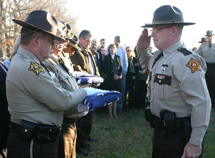 An American flag draped the coffin for Deputy Anthony Rakes, who was killed Nov. 14. After it was folded, Adam Rainwater, right, of the Green County Sheriff's Department presented the flag to Marion County Sheriff Jimmy Clements.