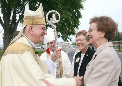 Archbishop of Louisville Joseph Kurtz, left, greets Ursuline Sisters Amelia Stenger and Susan Mary Mudd in front of the David R. Hourigan Government Building during the dedication of a memorial commemorating 100 years of service in Marion County by the Ursuline Sisters of Mt. St. Joseph. Rev. William Medley (left), the bishop of Owensboro, is in the background.