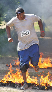 Desmond Spalding jumps through the Warrior Roast, one of the obstacles during the Warrior Dash in June at Pope's Creek Ranch.