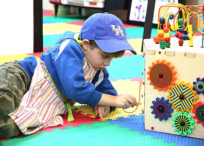 Cameron Knight takes a break from painting and plays with one of the toys at the autism center.