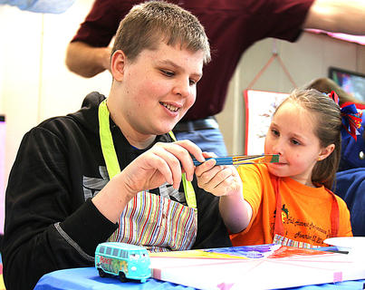 Zachary Moss gets some help from his sister, Kaitlyn, as they paint together.