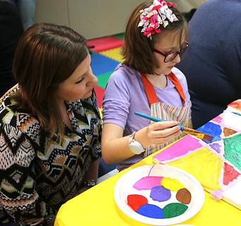 Pricilla Turner watches as her daughter, Isabella, works on her painting.