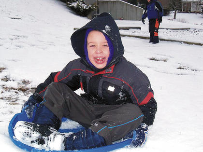Will Knight, 6, smiles big for the camera while sledding.