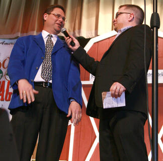 Brad Lanham, president of the Kentucky Fellowship of Musicians, and emcee Jeremy Bowman chat on stage about the history of the Kentucky Bluegrass Music Festival (and Lanham's blue jacket).