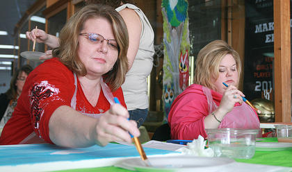Lisa Ford, left, and Gevette Riggs work on paintings during one of the new classes offered at this year's bluegrass festival.