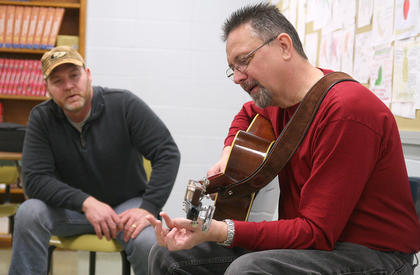 Carl Caldwell, right, of the Ricky Reece Band leads a guitar workshop Saturday afternoon at Marion County High School. John Reisinger of Loretto watches as Caldwell explains a technique.