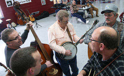 With so many musicians around, jam sessions were common throughout the bluegrass festival. Here, Dan Malone (banjo), Donnie Rodgers (guitar), Troy Beach (mandolin), Chase Collins (banjo) and Lynn Benningfield (bass) play a song in the Marion County High School cafeteria.