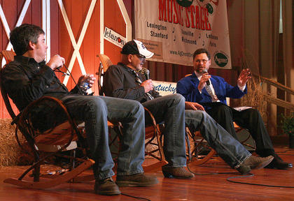 Brad Lanham (blue jacket) speaks with Sammy Shelor (center) and Brandon Rickman of the Lonesome River Band during a on-stage interview during Saturday evening's dinner show.