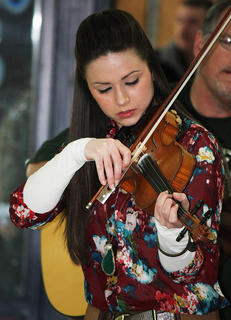 Charli Robertson, one of the performing band members and teachers, plays the violin in an example performance.