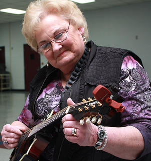 Wanda Runner of Bloomfield, Tenn., carefully tunes her mandolin before participating in a musical workshop Saturday morning.