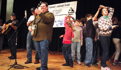 "Three-time national banjo picking champion Gary ""Biscuit"" Davis plays the banjo with members of the Kentucky Fellowship of Musicians as students from Calvary Elementary School show of their dancing skills."
