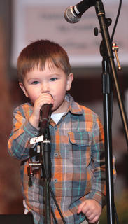 Anthony Wiser, 3, of Lebanon couldn't resist the stage. During the Hagar's Mountain Boys performance Friday evening at the Kentucky Bluegrass Music Kickoff, Wiser climbed the steps to the stage and tried singing into one of the shorter microphones.
