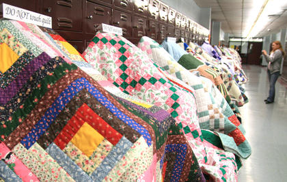 Stacey McClellan of Taylor County pauses to take a photo of a few quilts that were part of the Kentucky Bluegrass Quilt Show, a new feature at this year's Kentucky Bluegrass Music Kickoff.