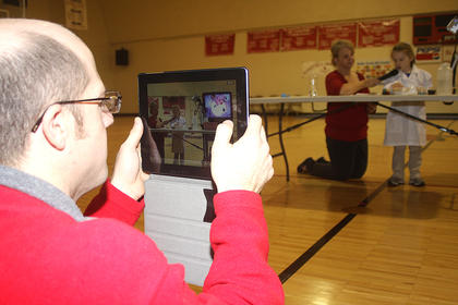 Jenna Mullins wows the crowd with her science experiments as her dad records her performance with his iPad.