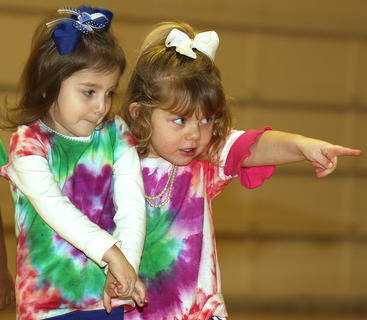 Kendall Thompson, left, has a little stage fright as Kylee Hickey points out someone special in the crowd. Both little girls are in pre-school at St. Augustine.