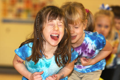 Sarah Ford sticks out her tongue and closes her eyes during her performance with her pre-school classmates. Also pictured is Piper Jones.