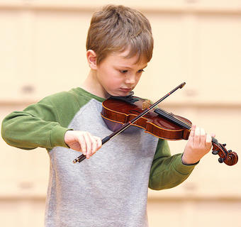 Second grader Elijah Winebrenner performs a violin solo.