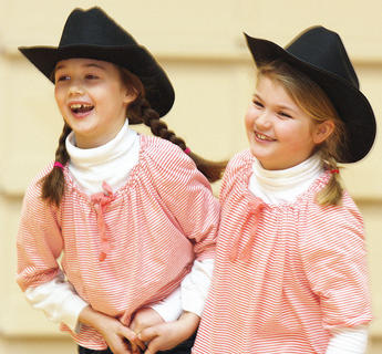 Third graders Libby Palagi and Shelby Hayden giggle after performing an original song and dance routine.