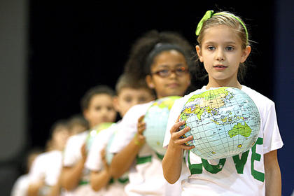 Alexandria Jeffries holds onto a blow-up replica of the planet Earth during the A.C. Glasscock Elementary student showcase. The event was canceled twice because of snow.