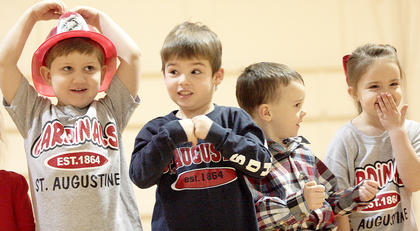 Preschoolers Braxton Benedict, Gavin Spalding, Ethan Essex, and Josie Mattingly join their classmates in singing a song about a big fire truck.