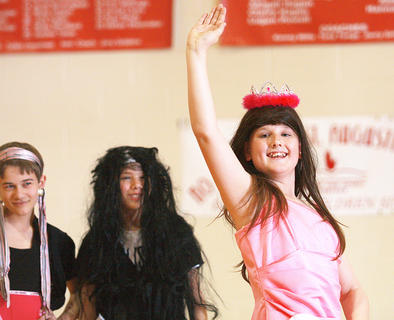 "Logan Peterson waves after winning a ""beauty pageant"" by the sixth-grade boys. Aaron Howard (left) and Zach Hunt are in the background. Aerosmith's ""Dude Looks Like a Lady"" accompanied the pageant."