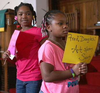 Deyera Spalding and Kentasia Bell carry signs with information about historic African-Americans.