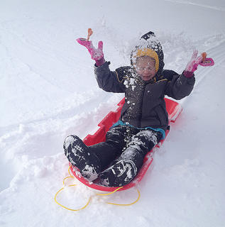 Adalyn Higdon, 5, frolics in the snow while going sleigh riding.