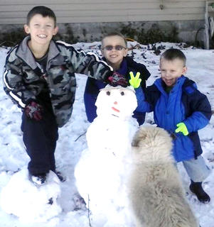 Pictured with their snowman is, from left, J.D., Kalvry and Jacobi Spalding. Rocky, the dog, snuck in to check out the snowman.