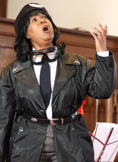 """The Marion County Arts and Humanities Council celebrated Black History Month Sunday with a Gospel Extravaganza at the Lebanon United Presbyterian Church in Lebanon. The event included gospel music presented by local and regional talent. Lebanon native Ruth Ann Fogle portrays Bessie Coleman, the daughter of a poor, southern, African American family, who became one of the most famous women and African Americans in aviation history. """"Brave Bessie"""" or """"Queen Bess,"""" as she became known, faced the double difficulties of racial and gender discrimination in early 20th-century America but overcame such challenges to become the first African American woman to earn a pilot's license."""